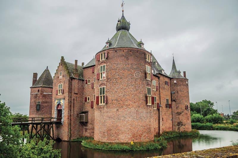 Средневековый замок Ammersoyen со своими башнями кирпича, деревянным мостом, водоналивным ровом и садами на пасмурный день стоковое фото rf