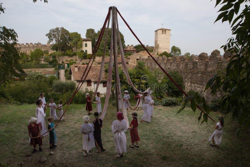 Средневековый танец с детьми в костюме вокруг поляка с лентами стоковое изображение