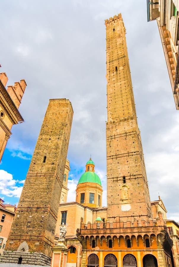 2 средневековых башни Болонья Le Должн Torri: Asinelli и Garisenda и церковь Chiesa di Сан Bartolomeo Gaetano стоковая фотография rf