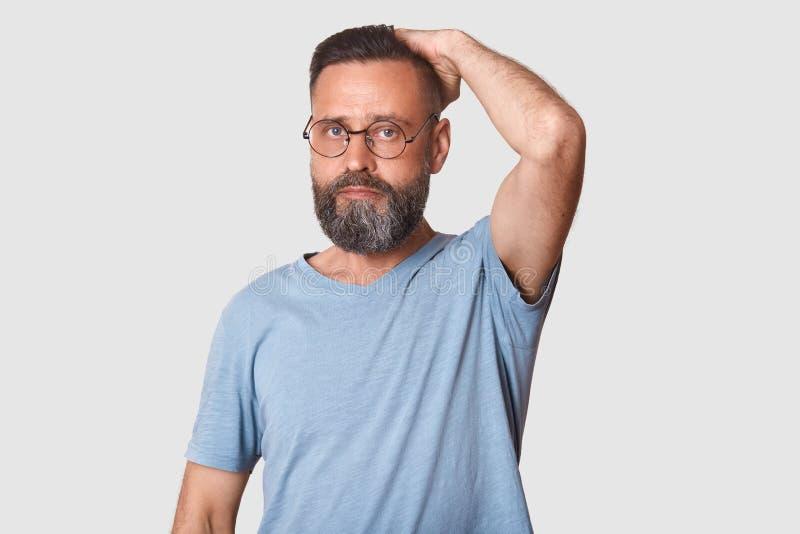 Среднее достигшее возраста хорошее выглядящ бородатым человеком с модными зрелищами нося свет - голубая случайная футболка, стоит стоковые изображения rf