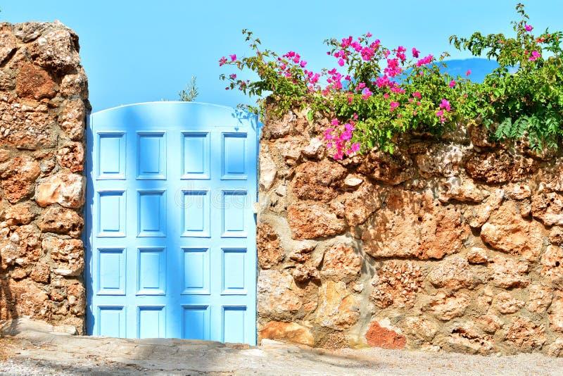 Среднеземноморская дверь стиля в каменной стене с красивыми цветками цветения стоковое изображение