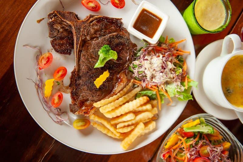 Средней прожарки зажаренный стейк T-косточки с салатом, французским картофелем фри, томатами, картофельным пюре и испеченным шпин стоковое изображение
