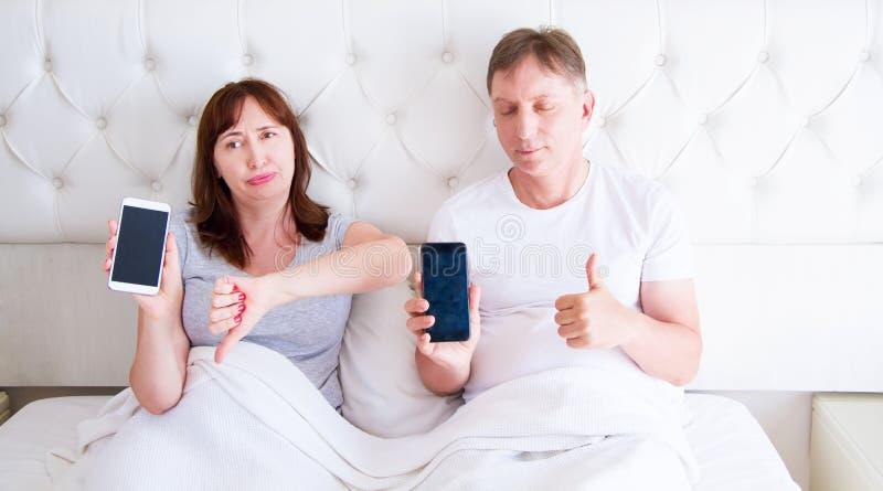 Средние достигшие возраста пары держа мобильный телефон пустого экрана и лежа на кровати в спальне гостиничного номера стоковое фото rf