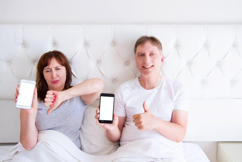 Средние достигшие возраста пары держа мобильный телефон пустого экрана и лежа на кровати в спальне гостиничного номера стоковые изображения rf