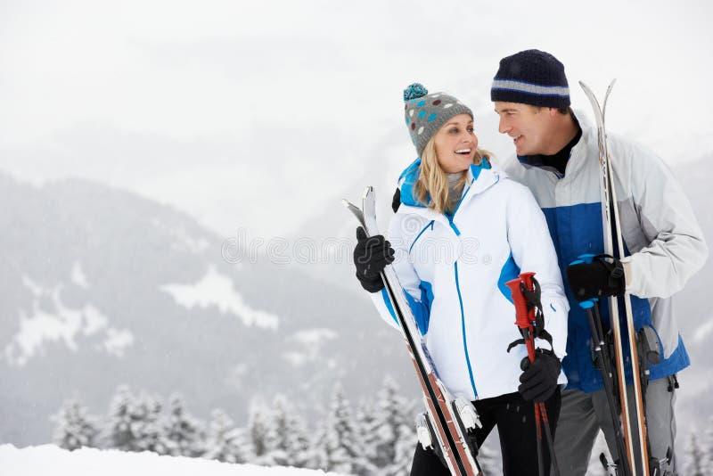 Средние постаретые пары на празднике лыжи в горах стоковое изображение rf