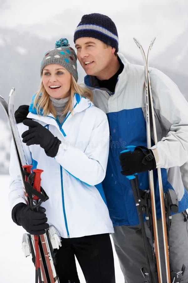 Средние постаретые пары на празднике лыжи в горах стоковое изображение