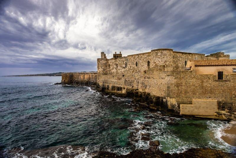Средний достигший возраста замок Maniace на береге моря в острове Ortigia на Сицилии, Siracusa стоковые изображения