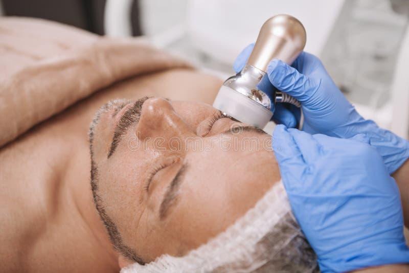 Средний-достигший возраста мужской клиент наслаждаясь обработкой косметологии оборудования стоковая фотография rf