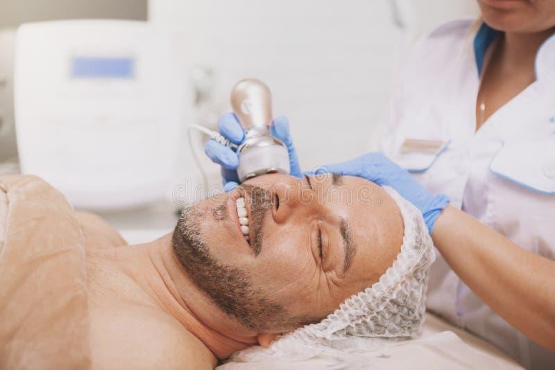 Средний-достигший возраста мужской клиент наслаждаясь обработкой косметологии оборудования стоковое фото rf