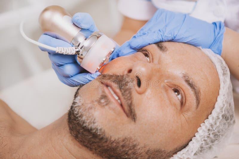 Средний-достигший возраста мужской клиент наслаждаясь обработкой косметологии оборудования стоковое изображение rf