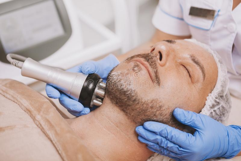 Средний-достигший возраста мужской клиент наслаждаясь обработкой косметологии оборудования стоковые изображения