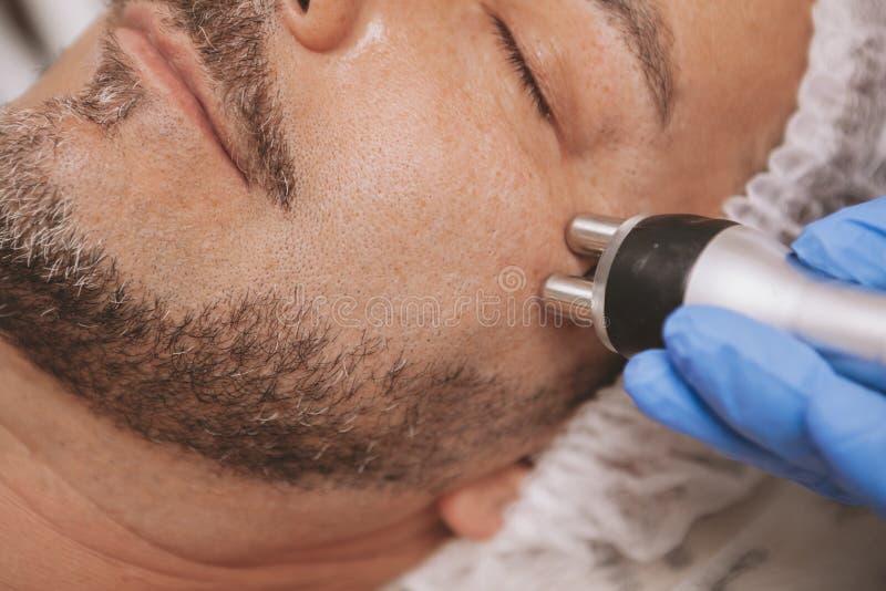 Средний-достигший возраста мужской клиент наслаждаясь обработкой косметологии оборудования стоковые изображения rf
