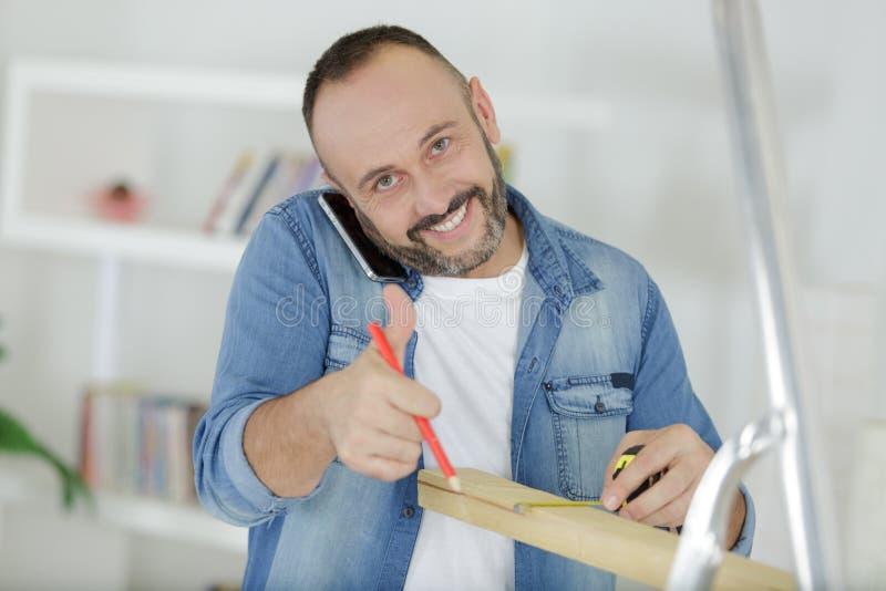 Средний достигший возраста плотник работая на ноутбуке в мастерской стоковое изображение rf