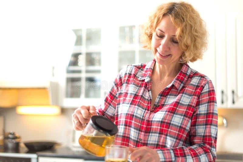 Средний достигший возраста чай женщины лить стоковое фото