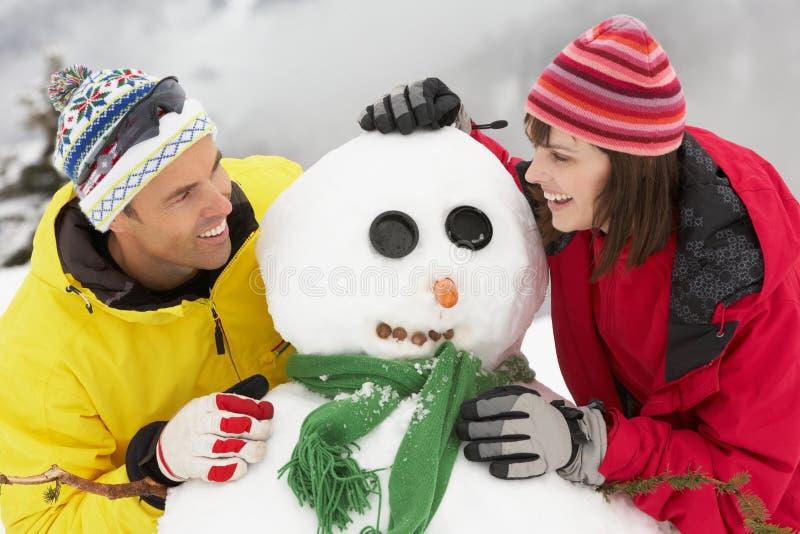 Средний постаретый снеговик здания пар на празднике лыжи стоковая фотография