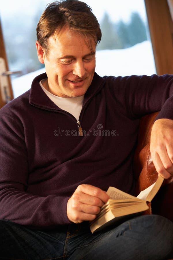 Средний постаретый человек ослабляя при книга сидя на софе стоковые фотографии rf