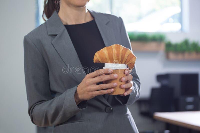 Средний раздел женских исполнительных держа кофе и круассана стоковое фото