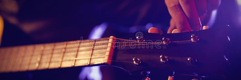 Средний раздел человека с гитарой на клубе стоковое фото