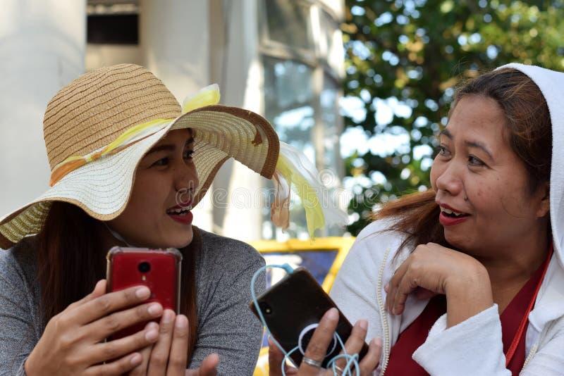 2 2 средних достигших возраста женщины имея потеху деля мысли и рассказы держа умный телефон стоковые фото
