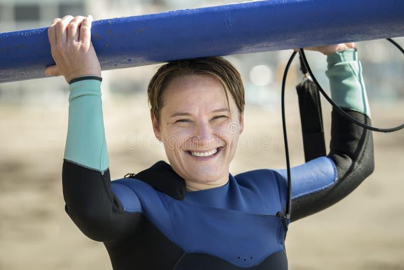 Средняя достигшая возраста женщина в surfboard удерживания мокрой одежды стоковое изображение rf