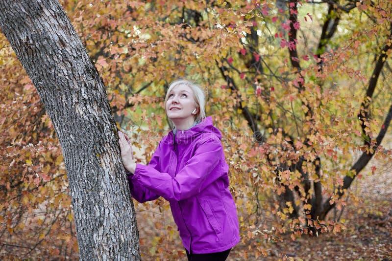 Средняя достигшая возраста кавказская женщина стоит самостоятельно близко к дереву на парке осени Руки на дереве, яркая случайная стоковая фотография rf