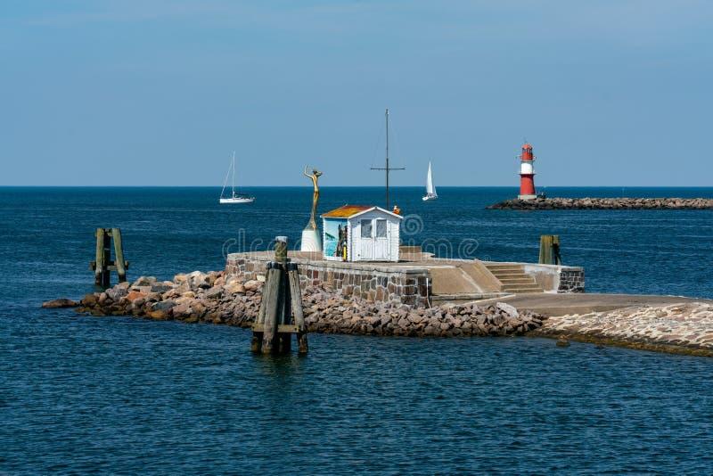 Средняя пристань в Warnemuende с красным маяком на заднем плане стоковая фотография rf