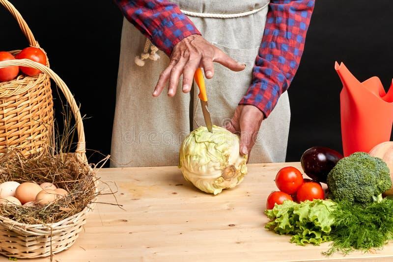 Средняя секция фермера в проверенной рубашке и рисбермы режа свежую капусту стоковая фотография rf