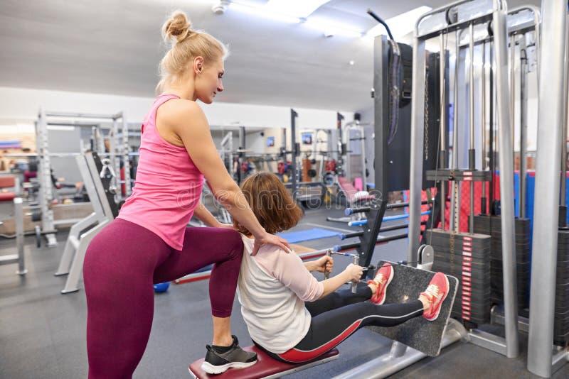 Средн-достигшая возраста женщина делая спорт работает в фитнес-центре Личный тренер спортзала помогая зрелой женщине Возраст спор стоковая фотография rf