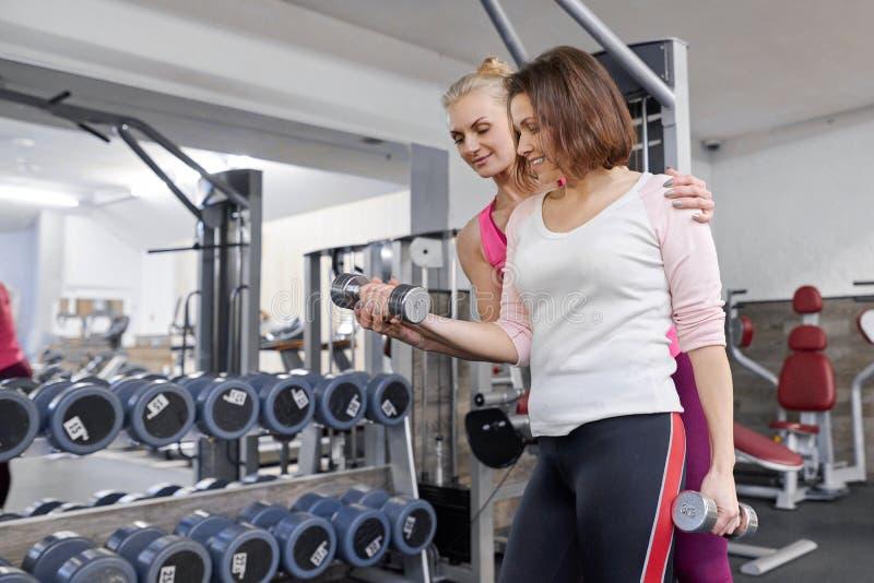 Средн-достигшая возраста женщина делая спорт работает в фитнес-центре Личный тренер спортзала помогая зрелой женщине Возраст спор стоковая фотография
