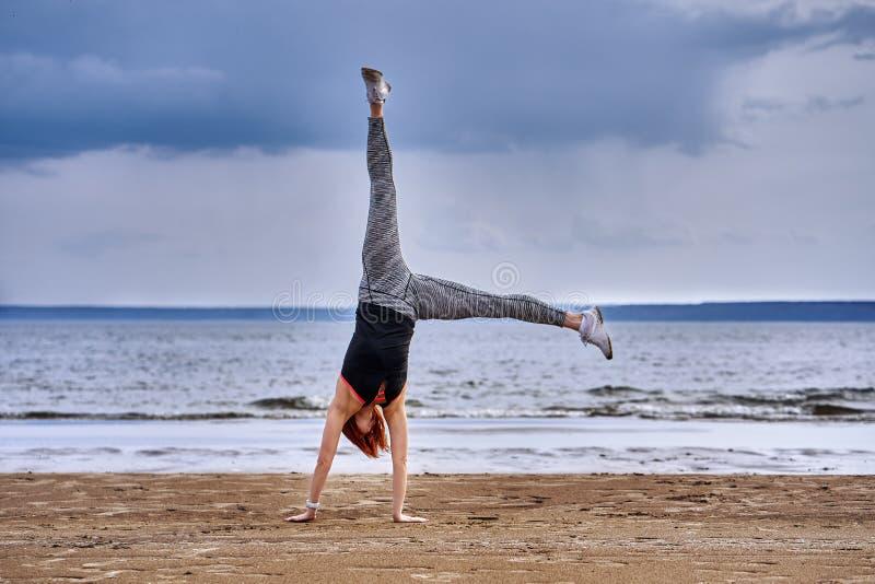 Средн-достигшая возраста женщина с красными волосами делает гимнастику на песочном береге большого реки стоковая фотография