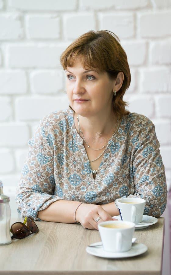 Средн-достигшая возраста женщина с чашкой кофе на таблице стоковые изображения