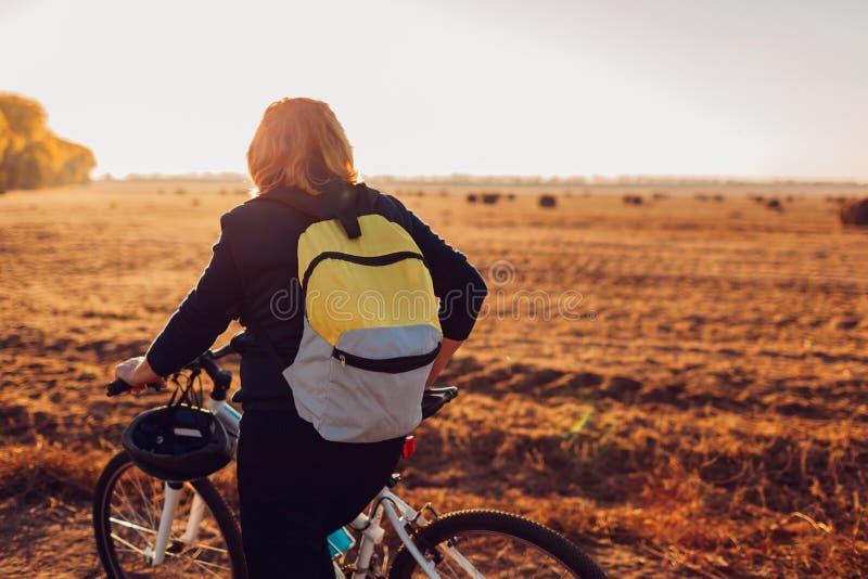 Средн-достигшее возраста катание велосипедиста женщины в поле осени на заходе солнца Старшая спортсменка восхищая взгляд стоковая фотография rf