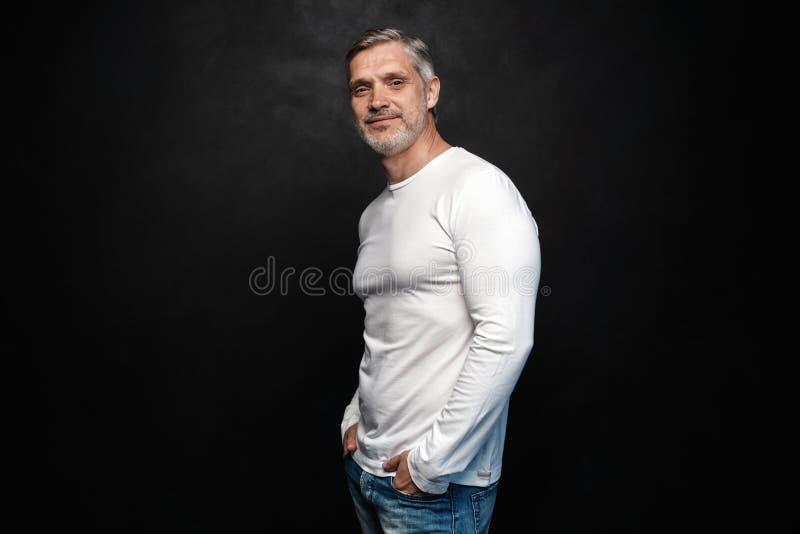 Средн-достигшее возраста хорошее смотрящ человека в белой футболке представляя перед черной предпосылкой с космосом экземпляра стоковое изображение rf