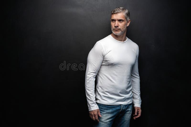 Средн-достигшее возраста хорошее смотрящ человека в белой футболке представляя перед черной предпосылкой с космосом экземпляра стоковые изображения
