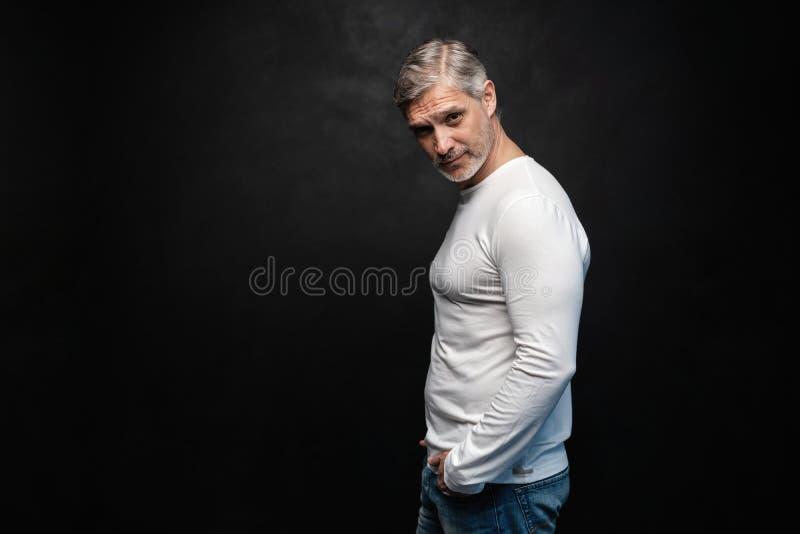 Средн-достигшее возраста хорошее смотрящ человека в белой футболке представляя перед черной предпосылкой с космосом экземпляра стоковые изображения rf
