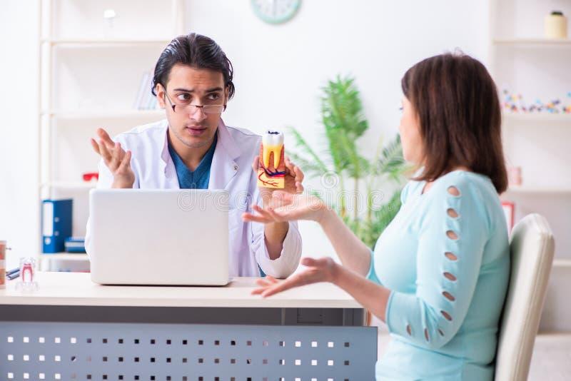 Средн-достигшее возраста stomatologist доктора женщины посещая мужское стоковые фотографии rf