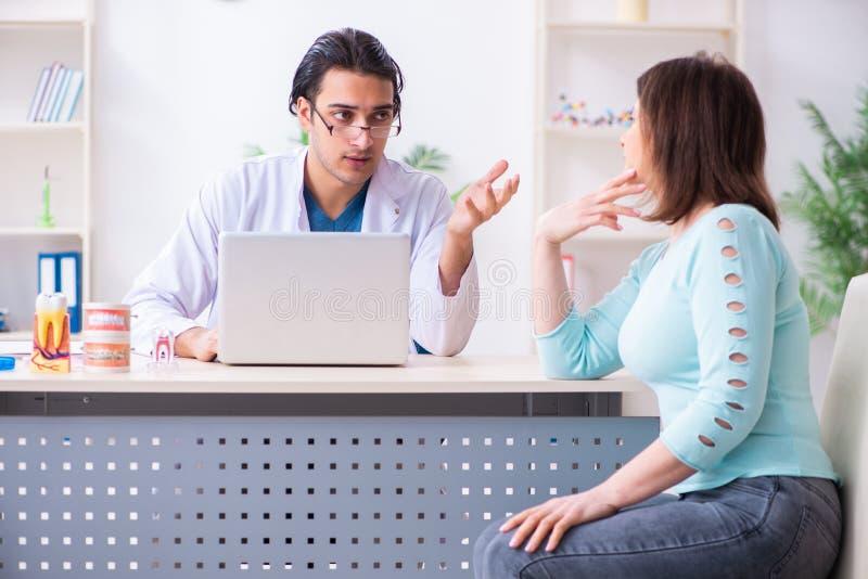 Средн-достигшее возраста stomatologist доктора женщины посещая мужское стоковая фотография rf