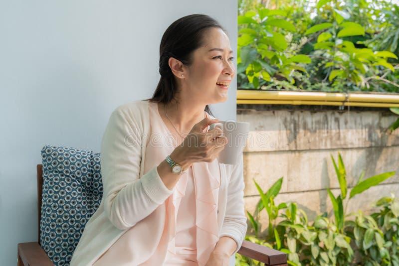 Средн-достигшие возраста азиатские женщины сидеть и кофе глоточка стоковые изображения rf