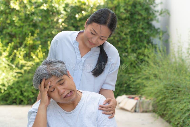 Средн-достигшие возраста и брюзгливые люди с параличом, изогнутым ртом, зубчиком руки и слабыми лимбами в кресло-коляске чувствуя стоковое фото rf