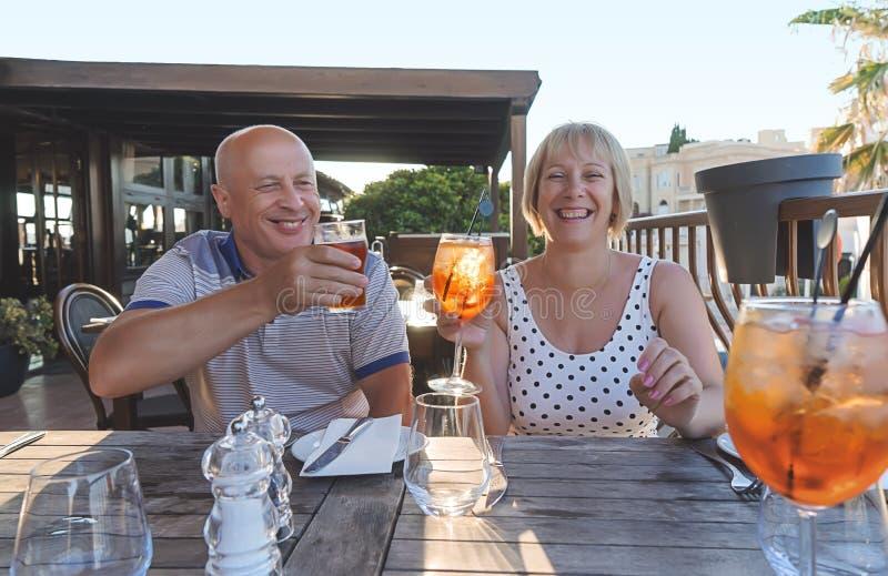Средн-достигшие возраста люди пар усмехаясь и наслаждаясь с напитками стоковая фотография