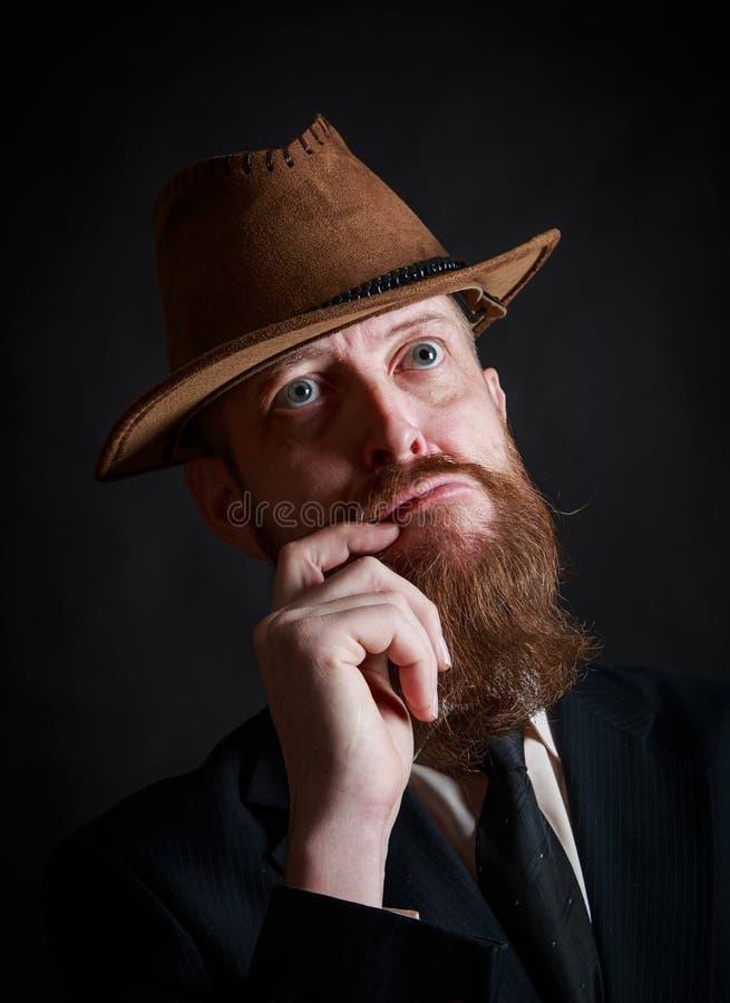 Средн-достигший возраста бородатый бизнесмен в шляпе и костюме смотря вверх с уверенным взглядом, нашел идея что он искал стоковая фотография