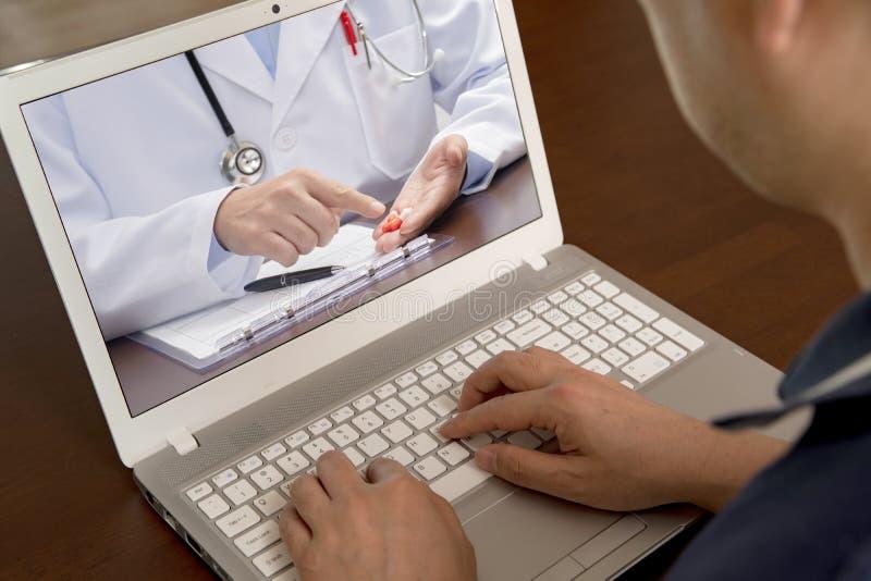 Средн-достигший возраста человек который использует телемедицину для того чтобы слушать доктора для лекарства стоковое фото rf