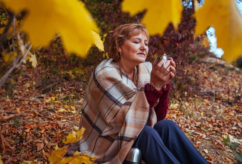 Средн-постаретая женщина выпивает чай в лесе осени стоковое изображение