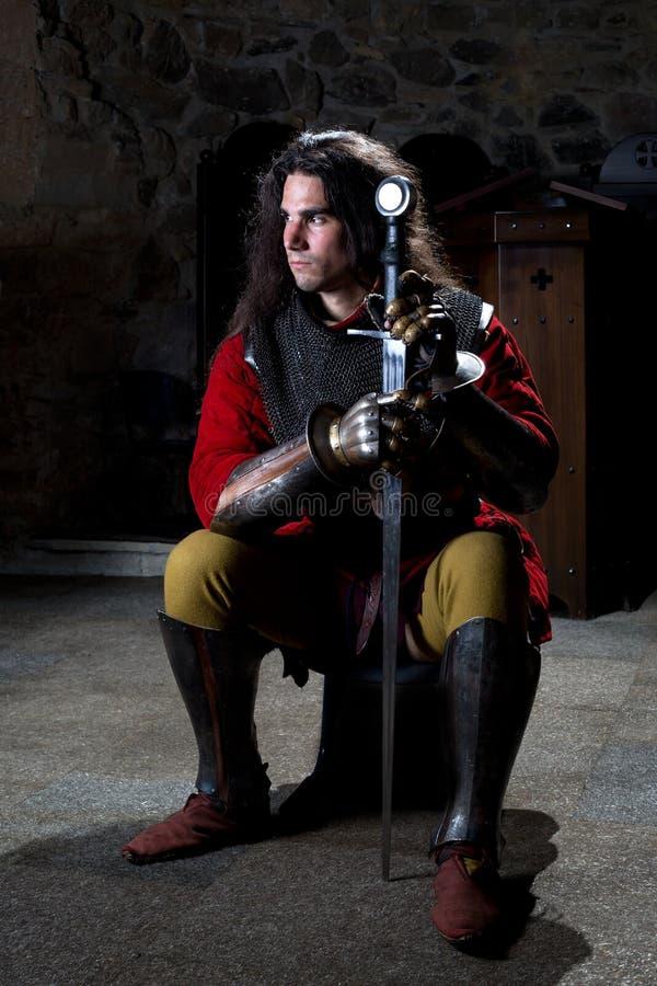 Средневековый ратник при шпага сидя в старой церков смотря прочь стоковые изображения rf