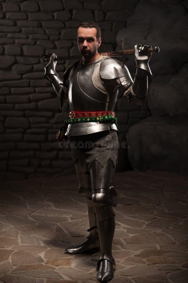 Средневековый рыцарь представляя с шпагой в темном камне стоковое изображение rf