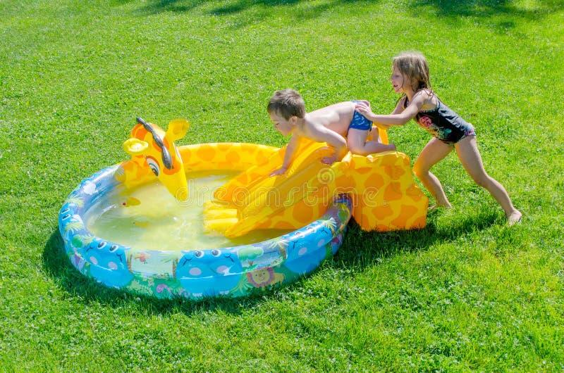 Средние сестра и брат в бассейне стоковое фото rf