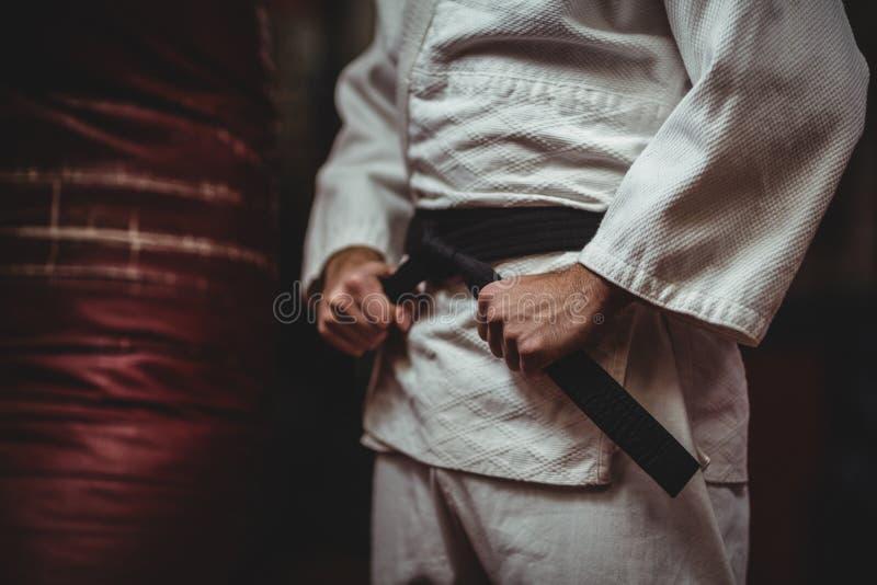 Средний раздел игрока карате связывая его пояс стоковые фотографии rf