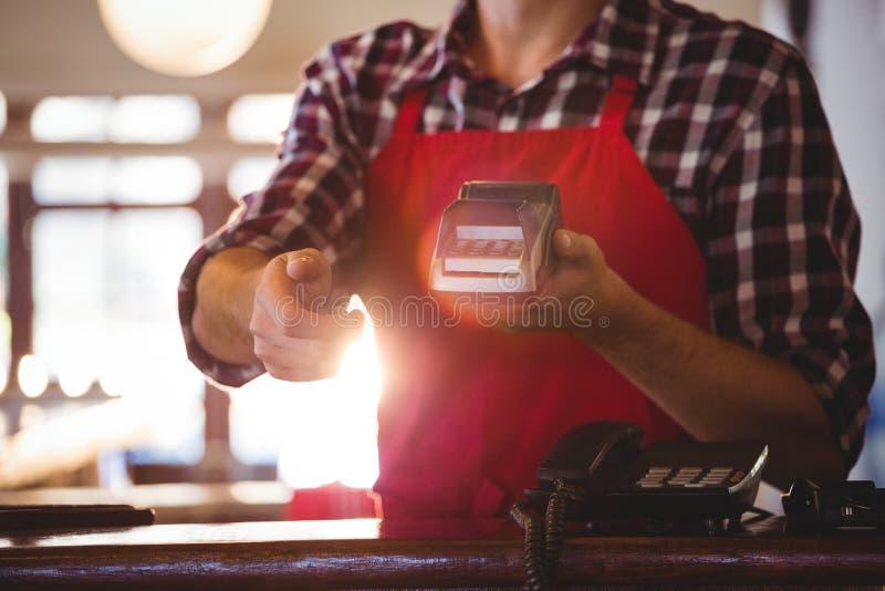 Средний раздел кельнера показывая машину кредитной карточки стоковое изображение