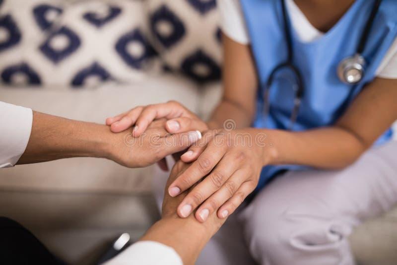 Средний раздел рук доктора касающих терпеливых стоковое фото
