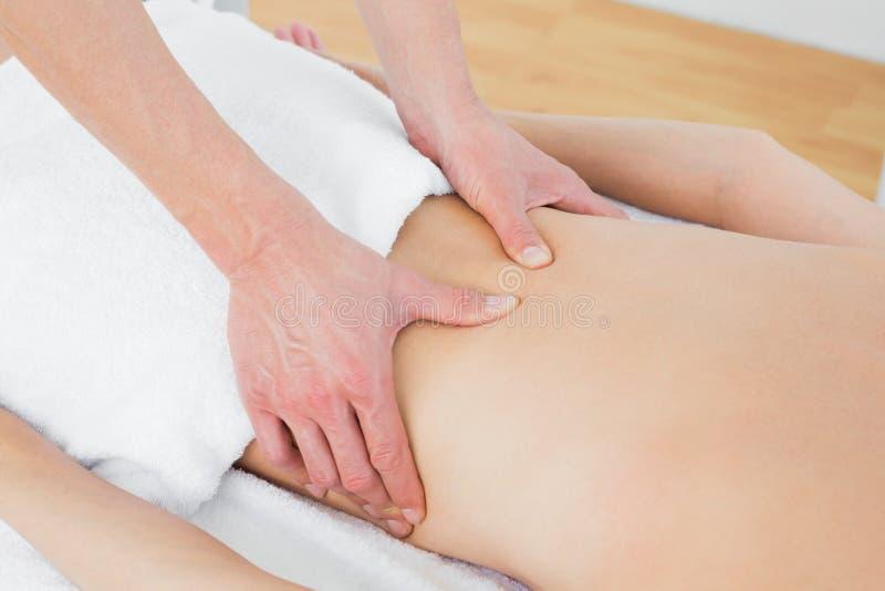 Средний раздел физиотерапевта массажируя заднюю часть женщины стоковые фото